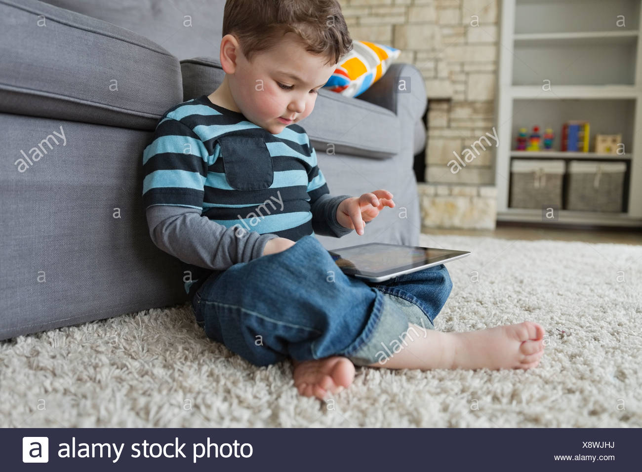 Little boy using digital tablet at home - Stock Image