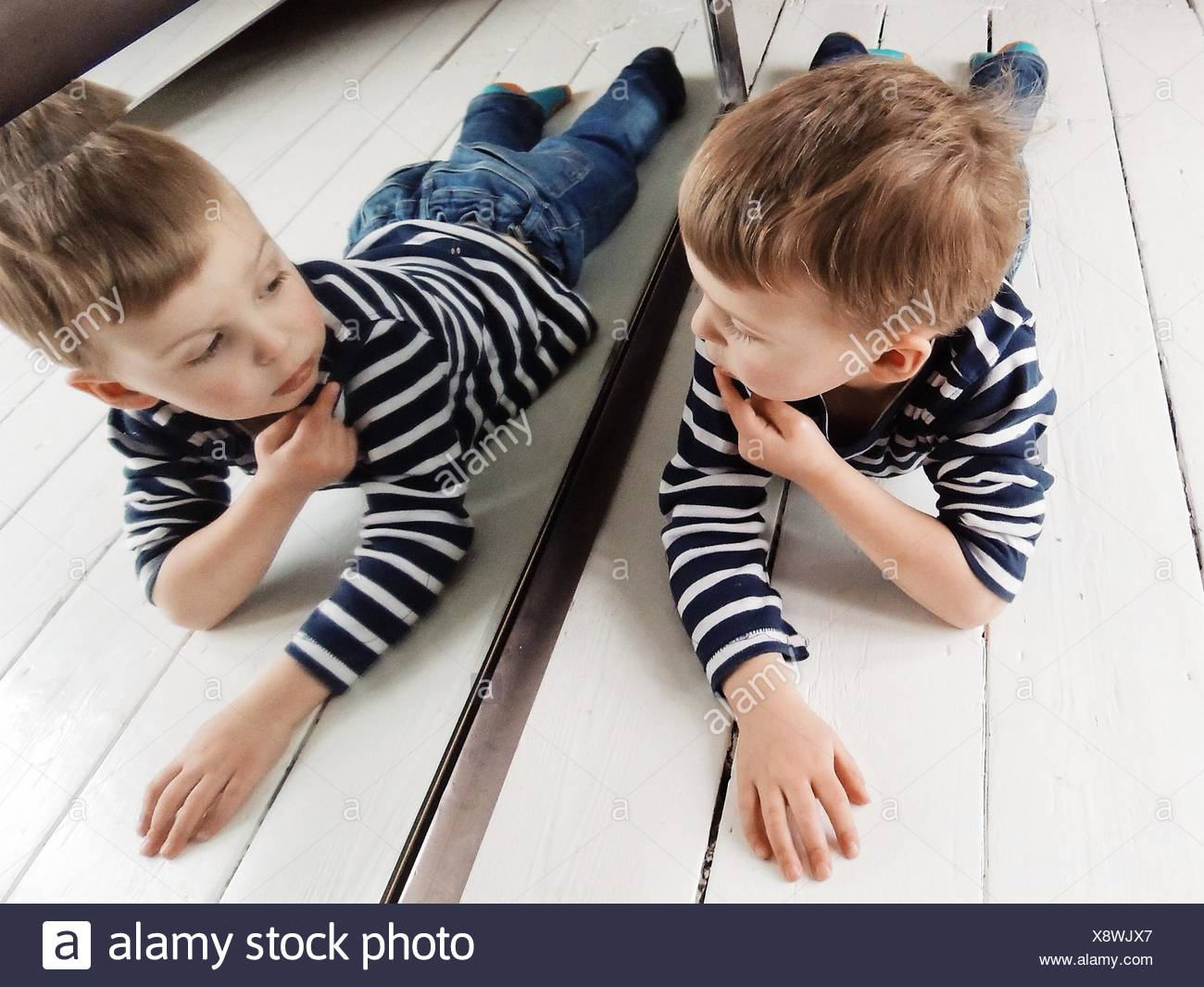 Portrait of a Boy lying on the floor looking at himself in the mirror - Stock Image