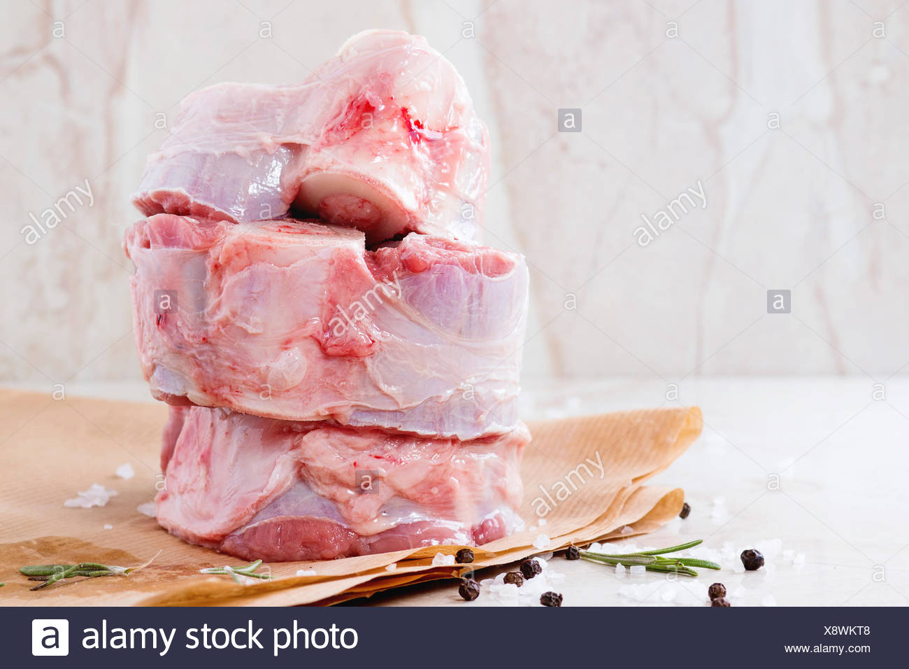 Stack of raw osso buco meat on crumpled paper with salt, pepper and rosemary over white marble as background Stock Photo