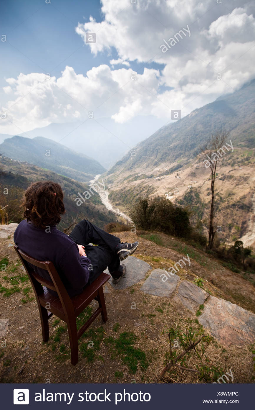 A trekker rests in a wooden chair to study the weather in a valley below. - Stock Image