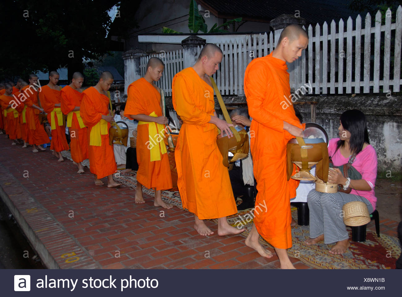 Buddhist monks with begging bowls receiving alms in the morning, Luang Prabang, Laos, Southeast Asia - Stock Image
