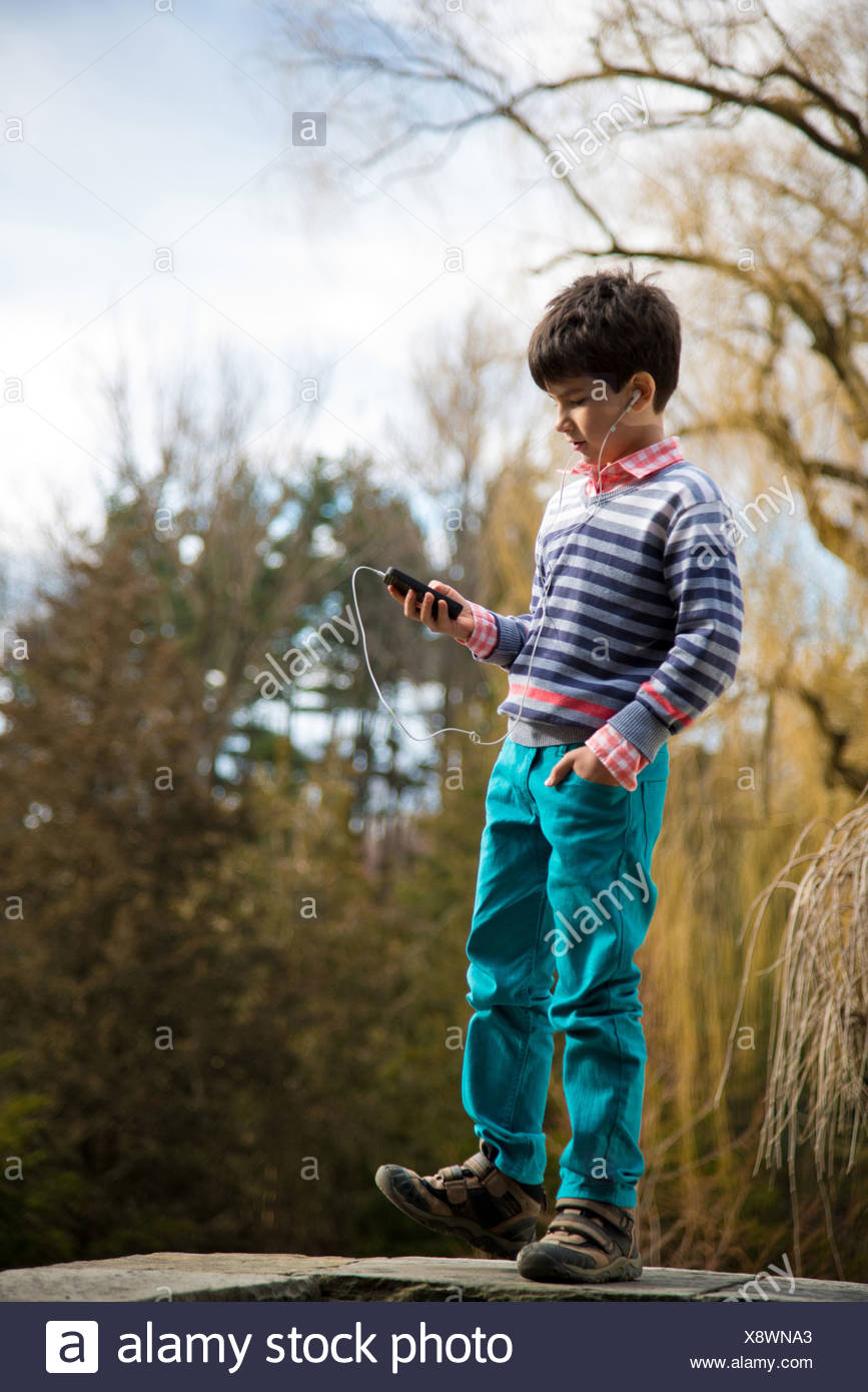 Boy playing on smartphone in playground - Stock Image