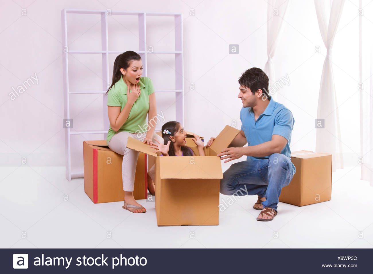Girl playing hide and seek with parents Stock Photo