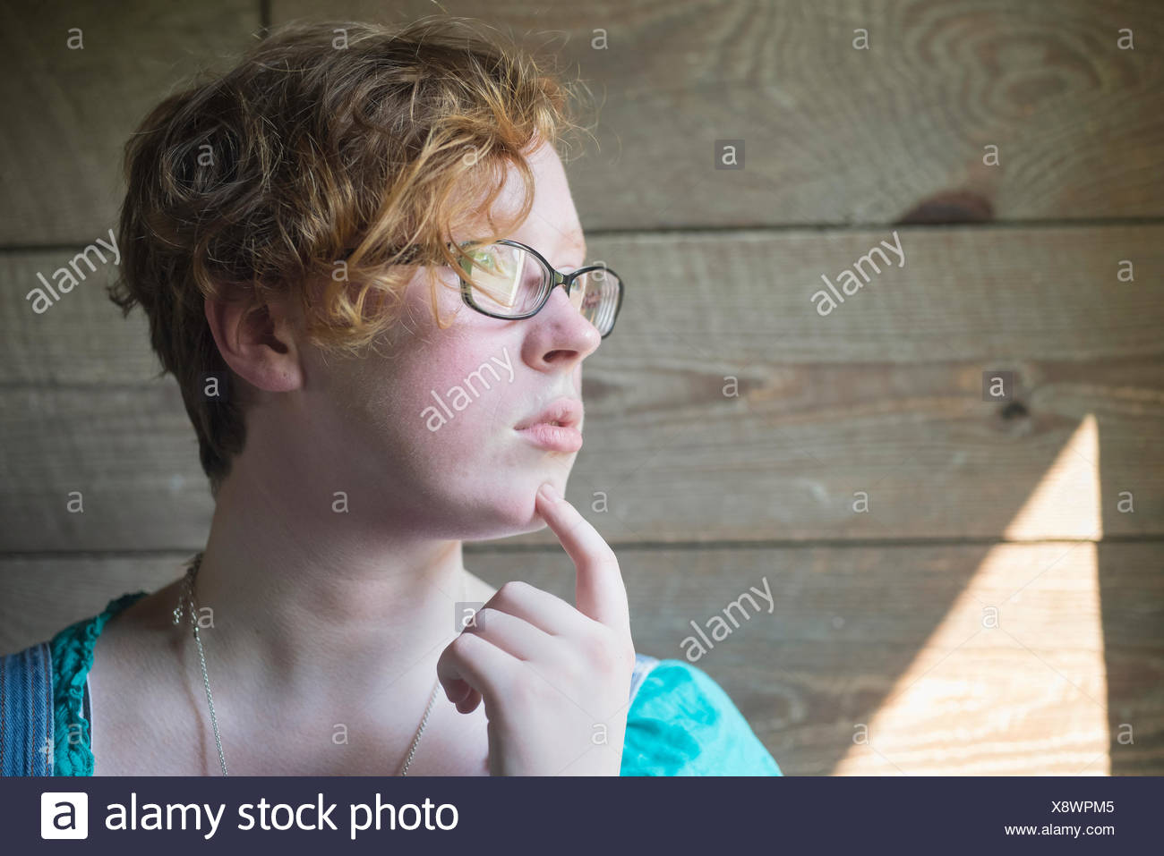 Portrait of a girl with curly red hair and eyeglasses standing against an old, wooden barn wall; Pittsboro, North Carolina, USA - Stock Image
