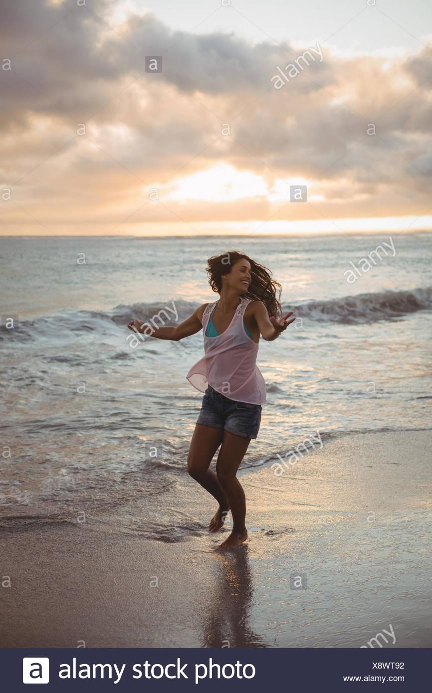 Beautiful woman having fun on the beach - Stock Image