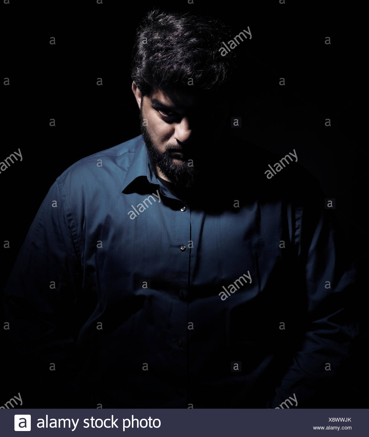 Dramatic shadowy portrait of a man - Stock Image