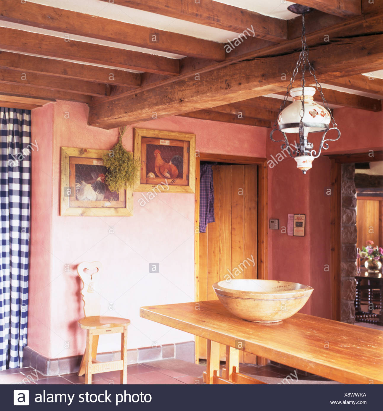 Victorian glass lamp above pine table in pink cottage dining ...