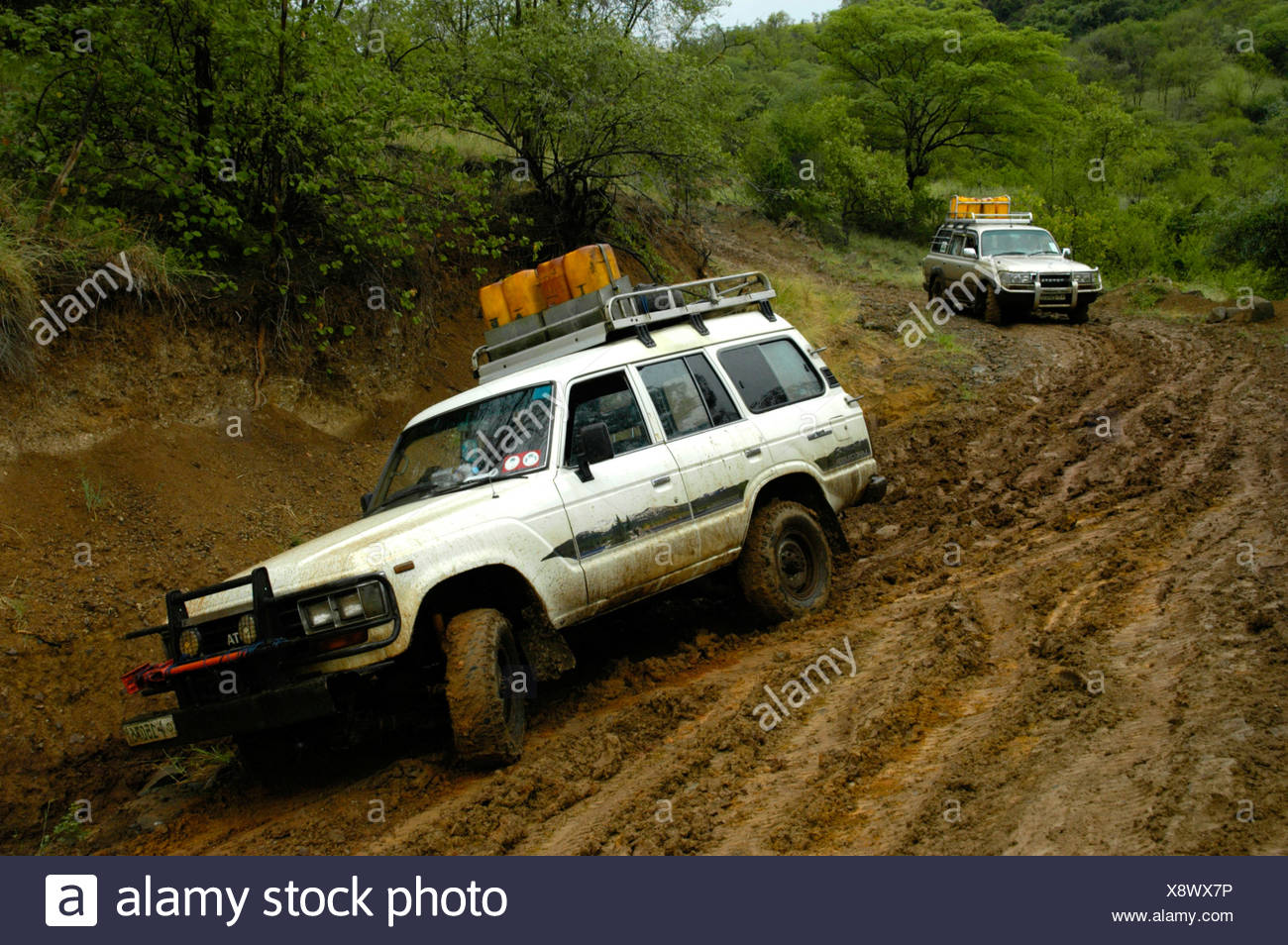 Two Toyota Landcruiser sliding down a muddy road near Jinka, Ethiopia, Africa - Stock Image
