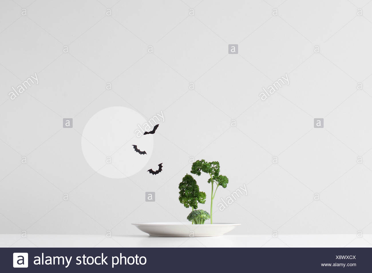 Conceptual spooky forest made up of green herbs and vegetables on a plate - Stock Image