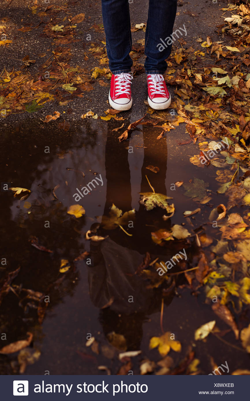 Woman standing by puddle in autumn park - Stock Image