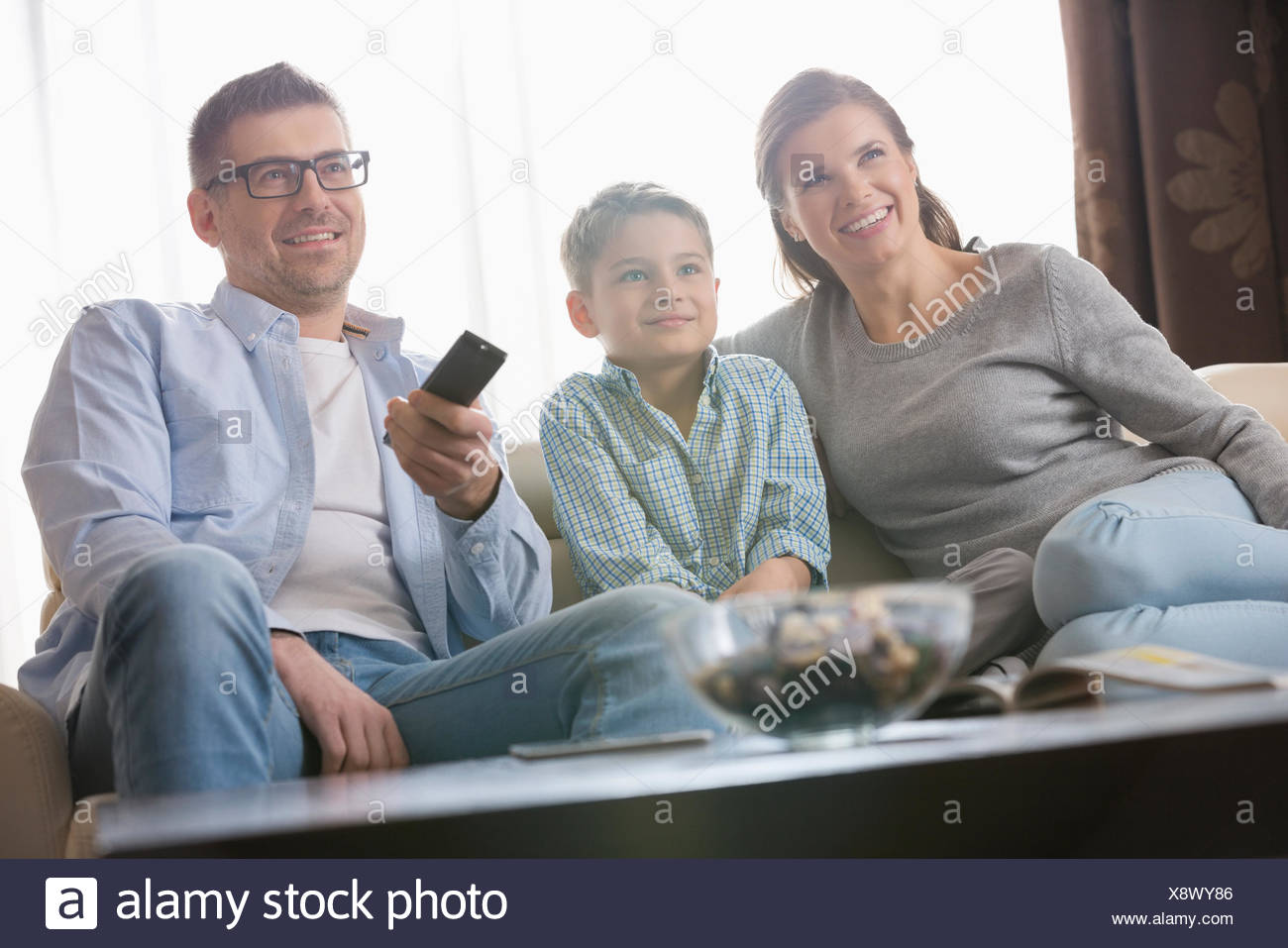 Boy watching TV with parents in living room - Stock Image