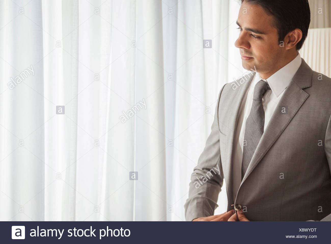 Businessman looking out of window - Stock Image