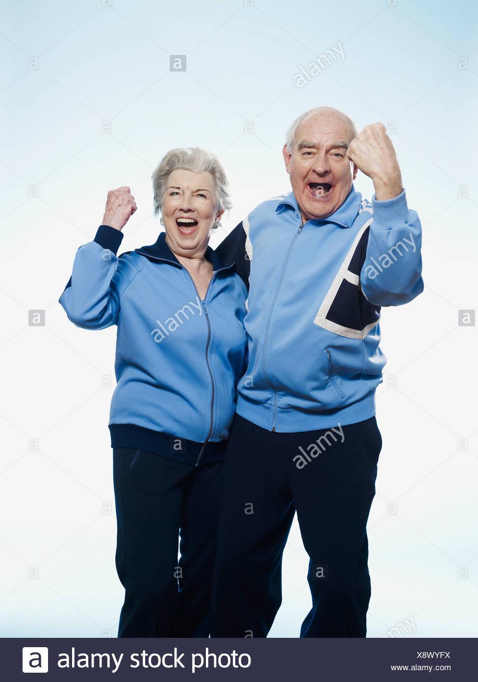Senior man and woman in sportswear cheering - Stock Image