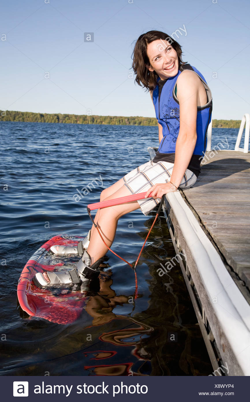 Woman sitting on dock with wakeboard - Stock Image