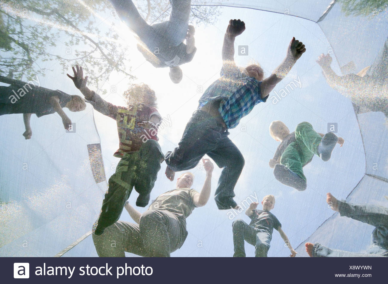 Mature men and boys jumping on trampoline, low angle view - Stock Image