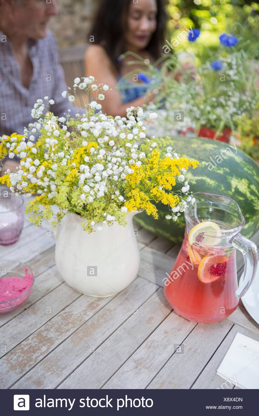Table laid for lunch, outdoors, senior couple in background - Stock Image