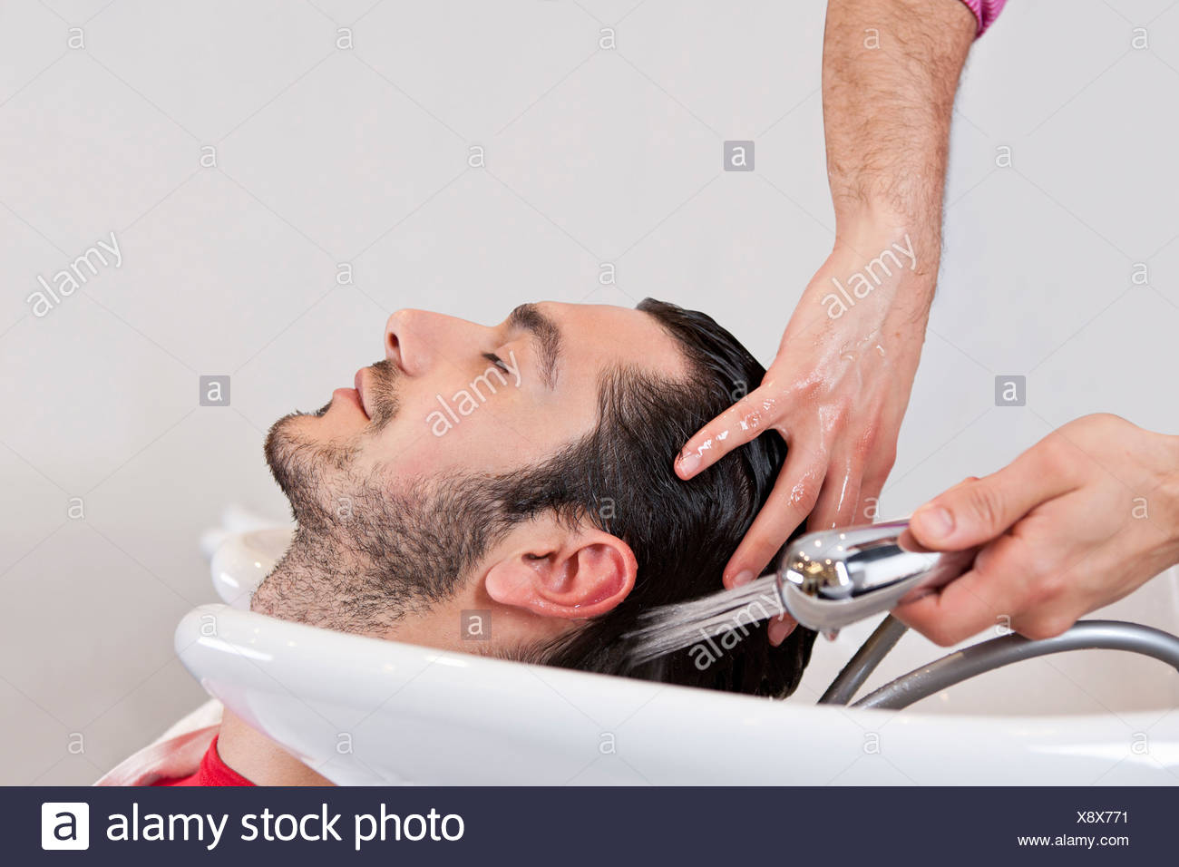 A male hairdresser washing a male clients hair, close up - Stock Image