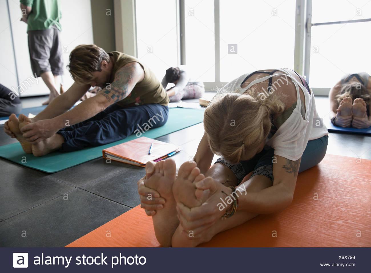 Woman practicing yoga seated fold in yoga class studio - Stock Image