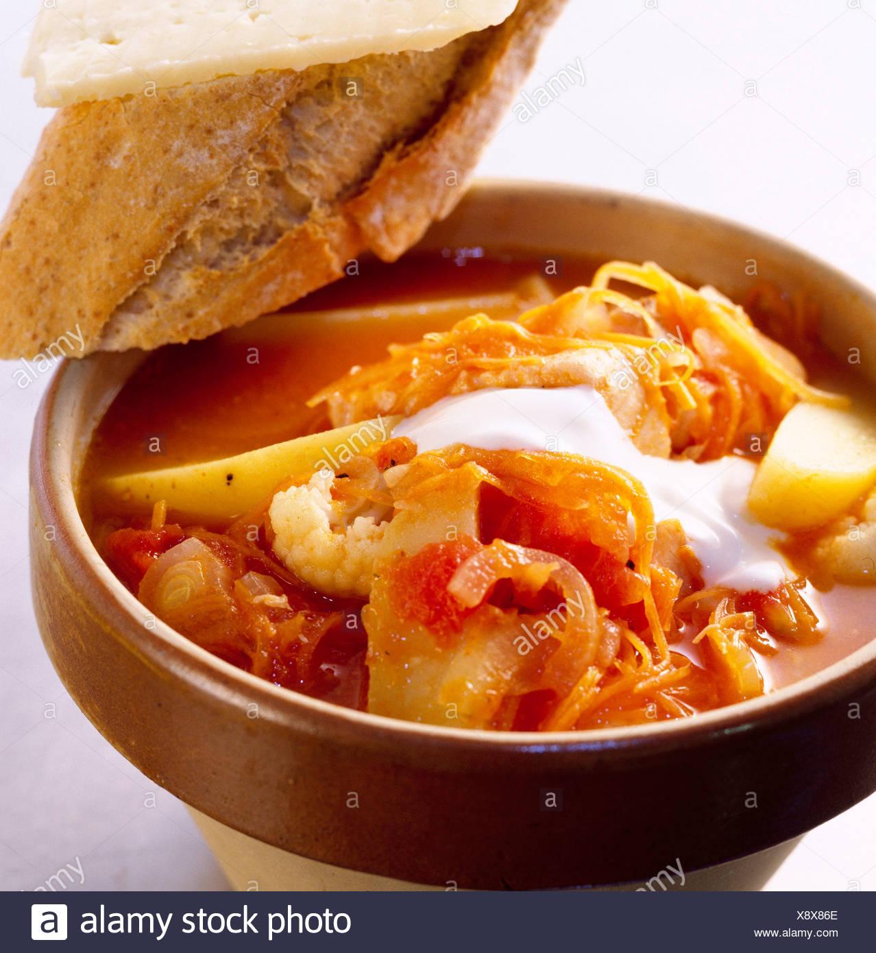 Midweek meals Fish casserole salmon, onion, carrots, tomatoes and potatoes yoghurt garnish in earthenware casserole dish chunk - Stock Image