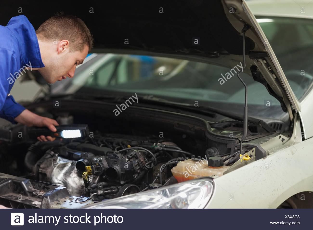 male mechanic with flashlight examining car engine stock photo