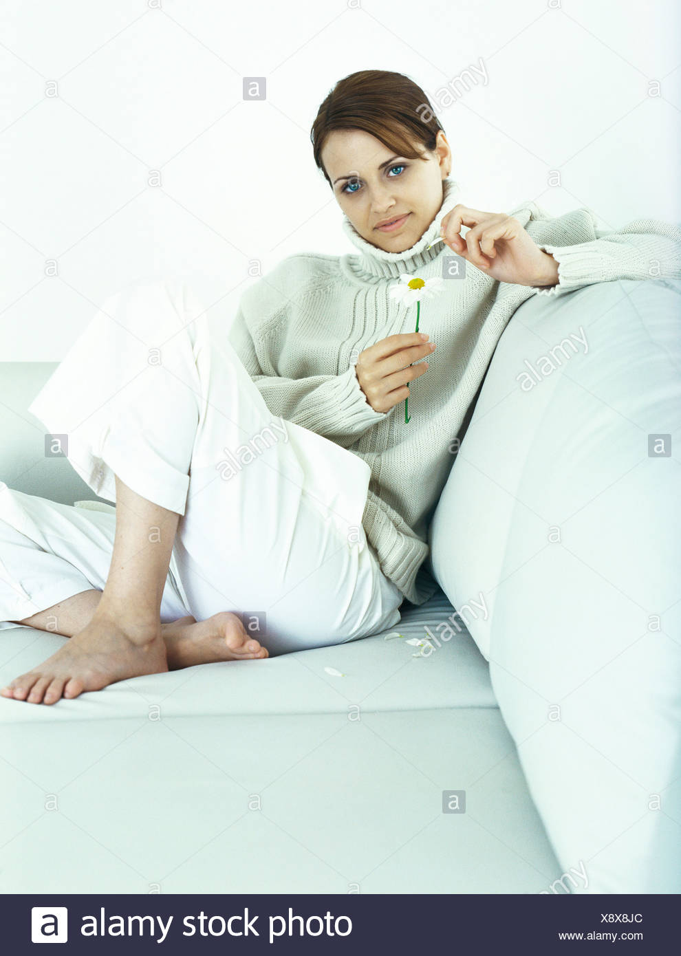 Woman sitting with knee up on sofa, plucking petals from daisy - Stock Image