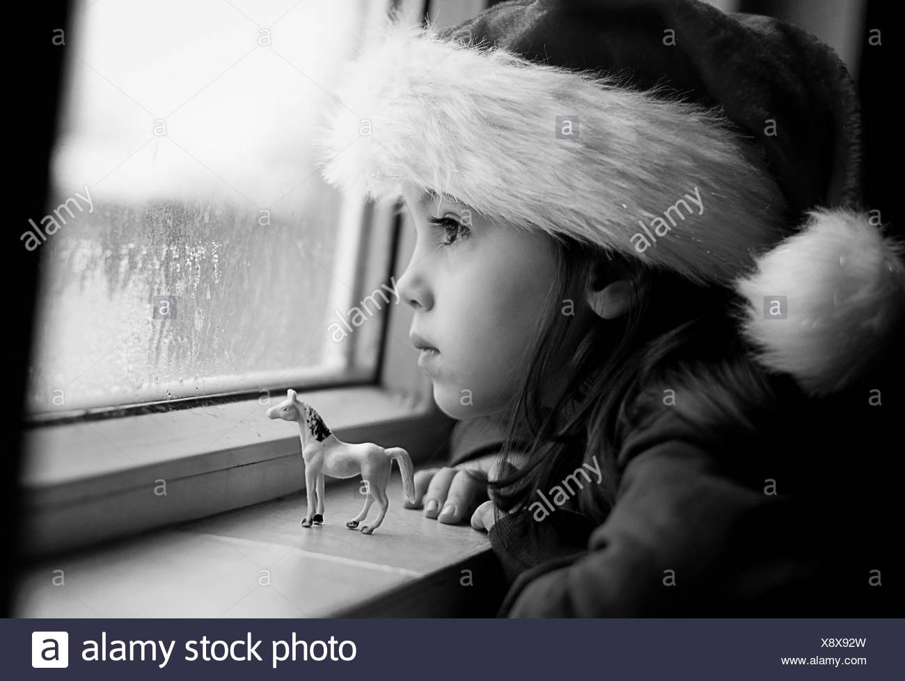 Girl wearing a Christmas hat looking out of the window Stock Photo