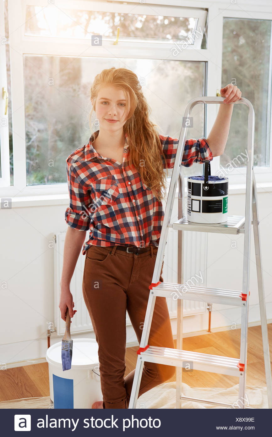 Portrait of teenage girl holding paint brush and step ladders - Stock Image