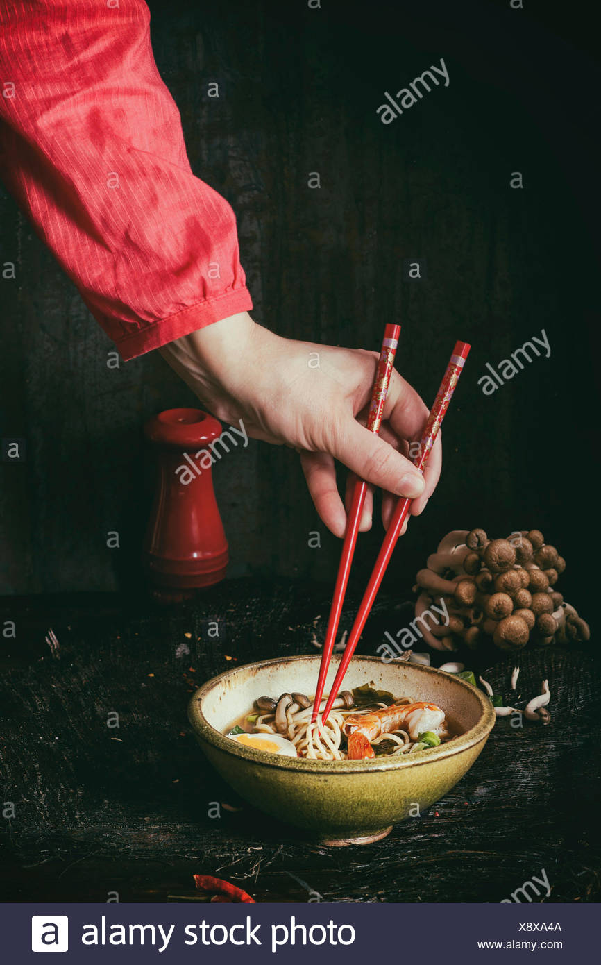 Female hand in red shirt take by red chopsticks noodles from asian ramen soup with shrimp, onion, sliced egg and mushrooms, serv - Stock Image