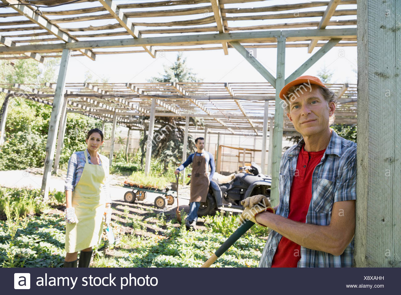 Portrait of confident workers tending to plants Stock Photo
