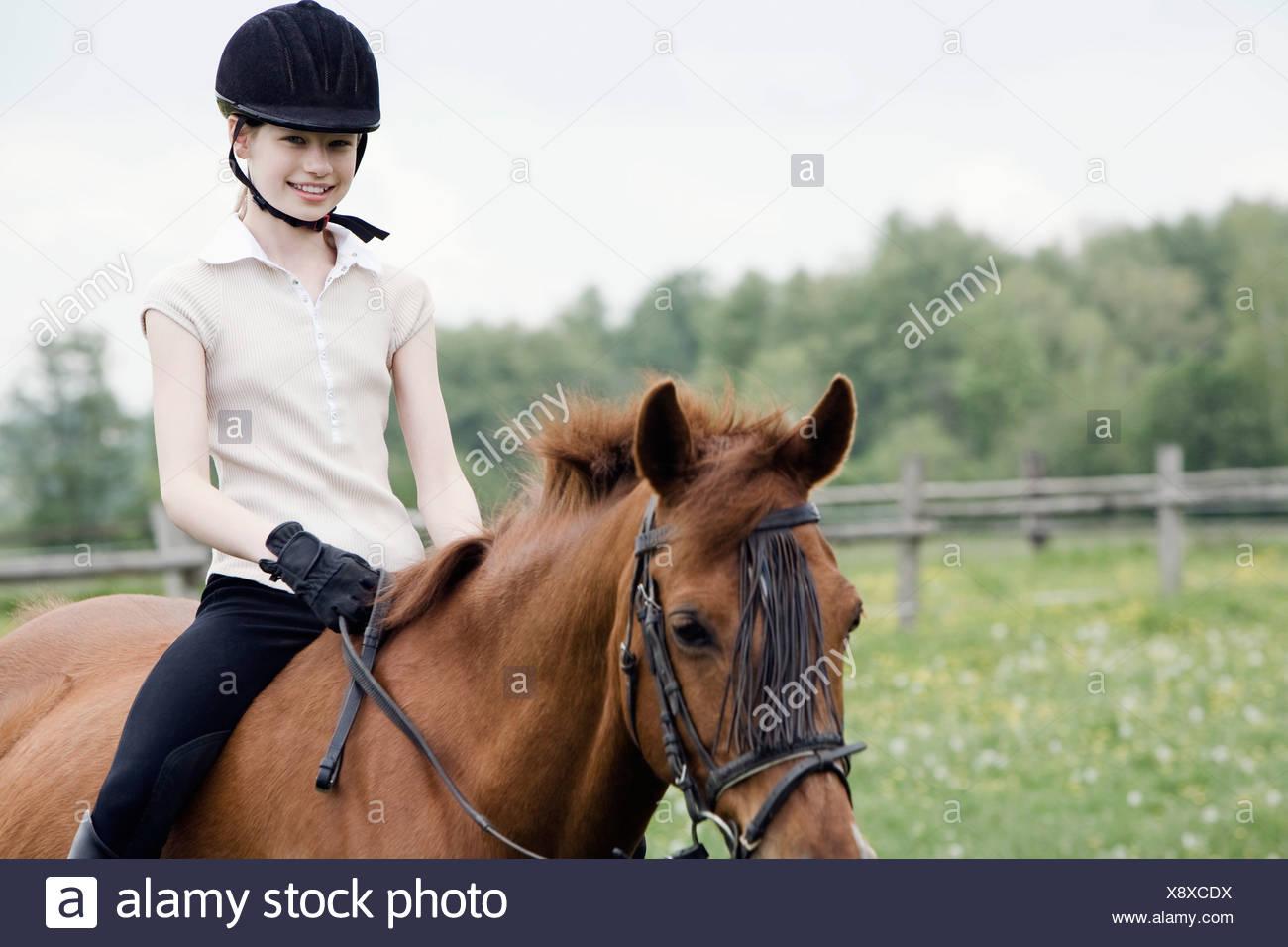 portrait of young girl doing horseback riding - Stock Image