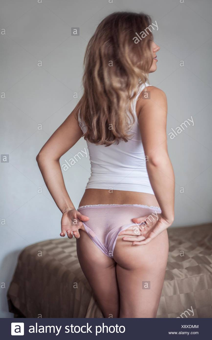 Backview of woman adjusting knickers - Stock Image
