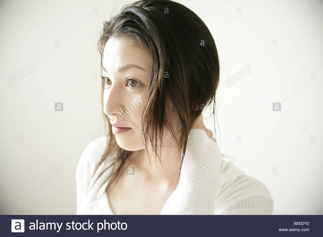 Close up of a young woman looking away - Stock Image