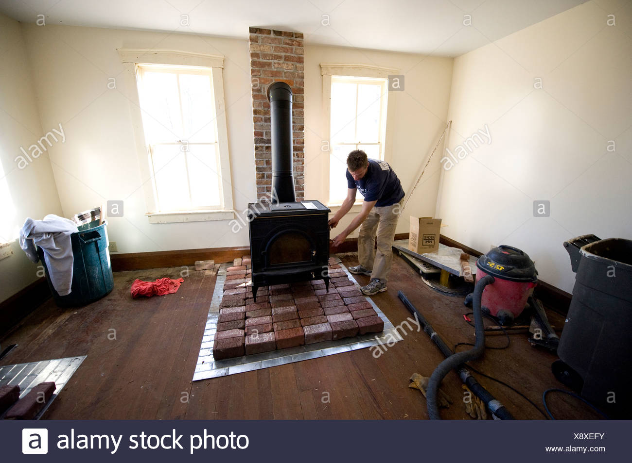 A man works on a wood stove in an old farmhouse in Dunbar, NE. - Stock Image