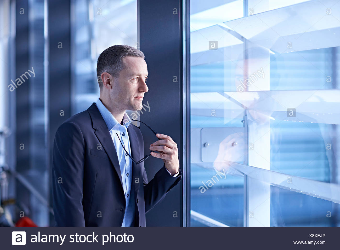 Businessman holding eyeglasses and looking through office window - Stock Image