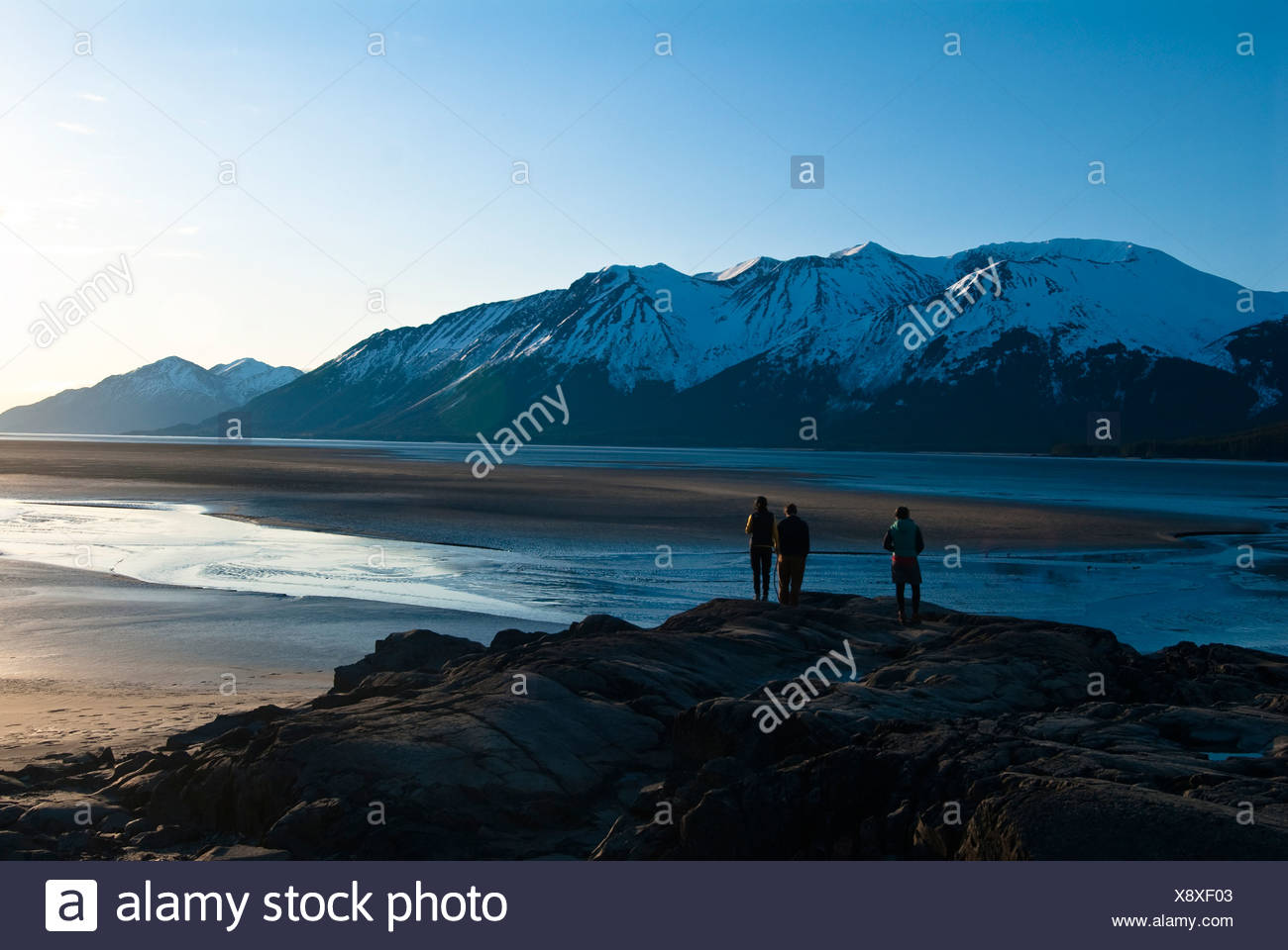 Alaska Turnagain Arm. tide out adventure evening group mudflats people rock several - Stock Image