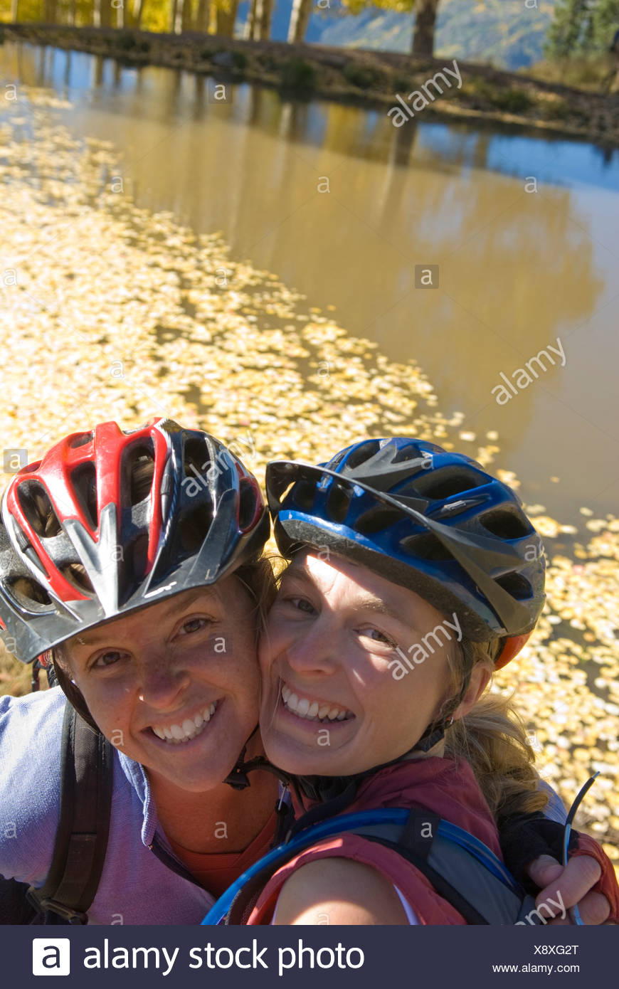 Two women posing next to lake with yellow aspen leaves, San Juan National Forest, Colorado. - Stock Image