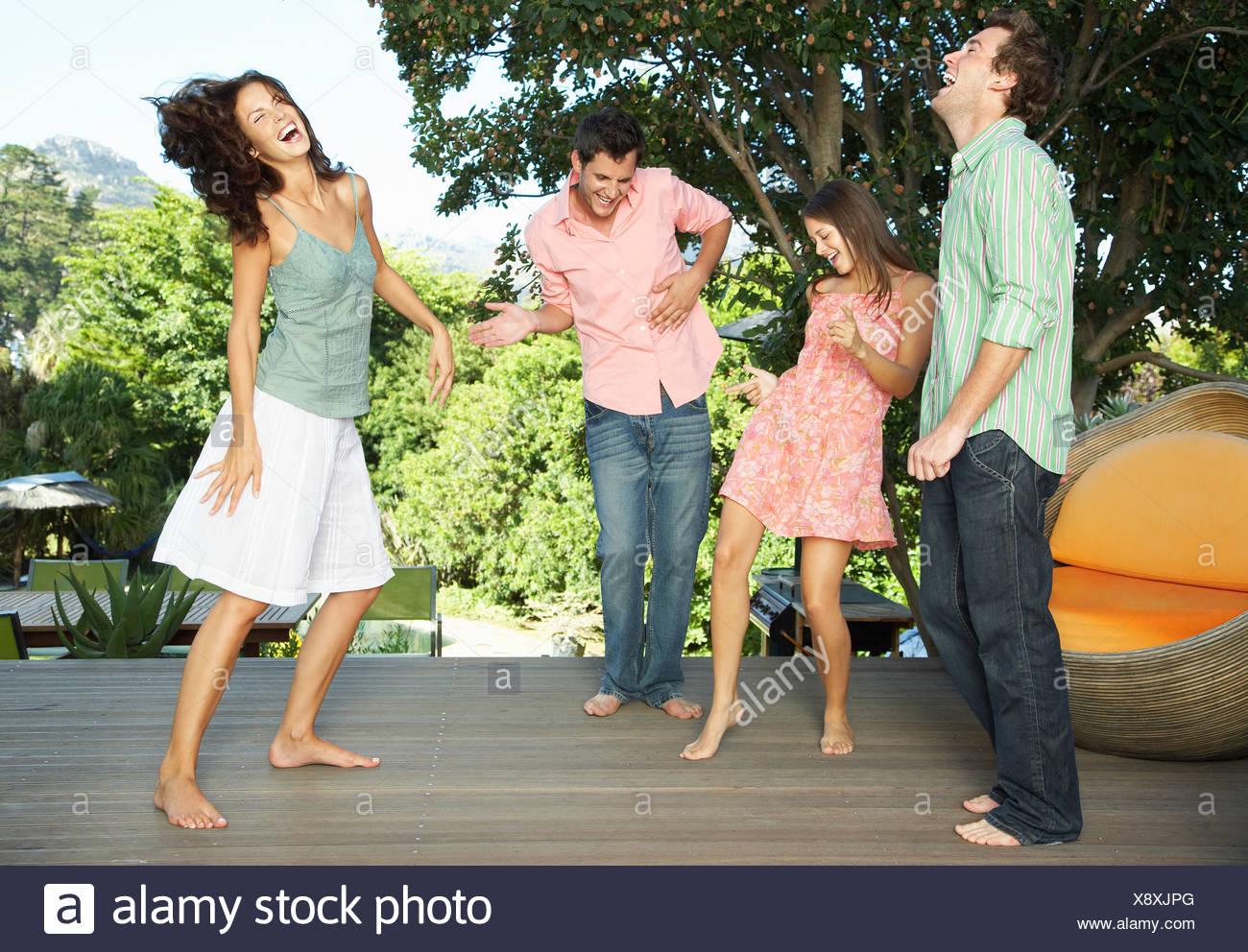 Friends dancing around on a deck - Stock Image