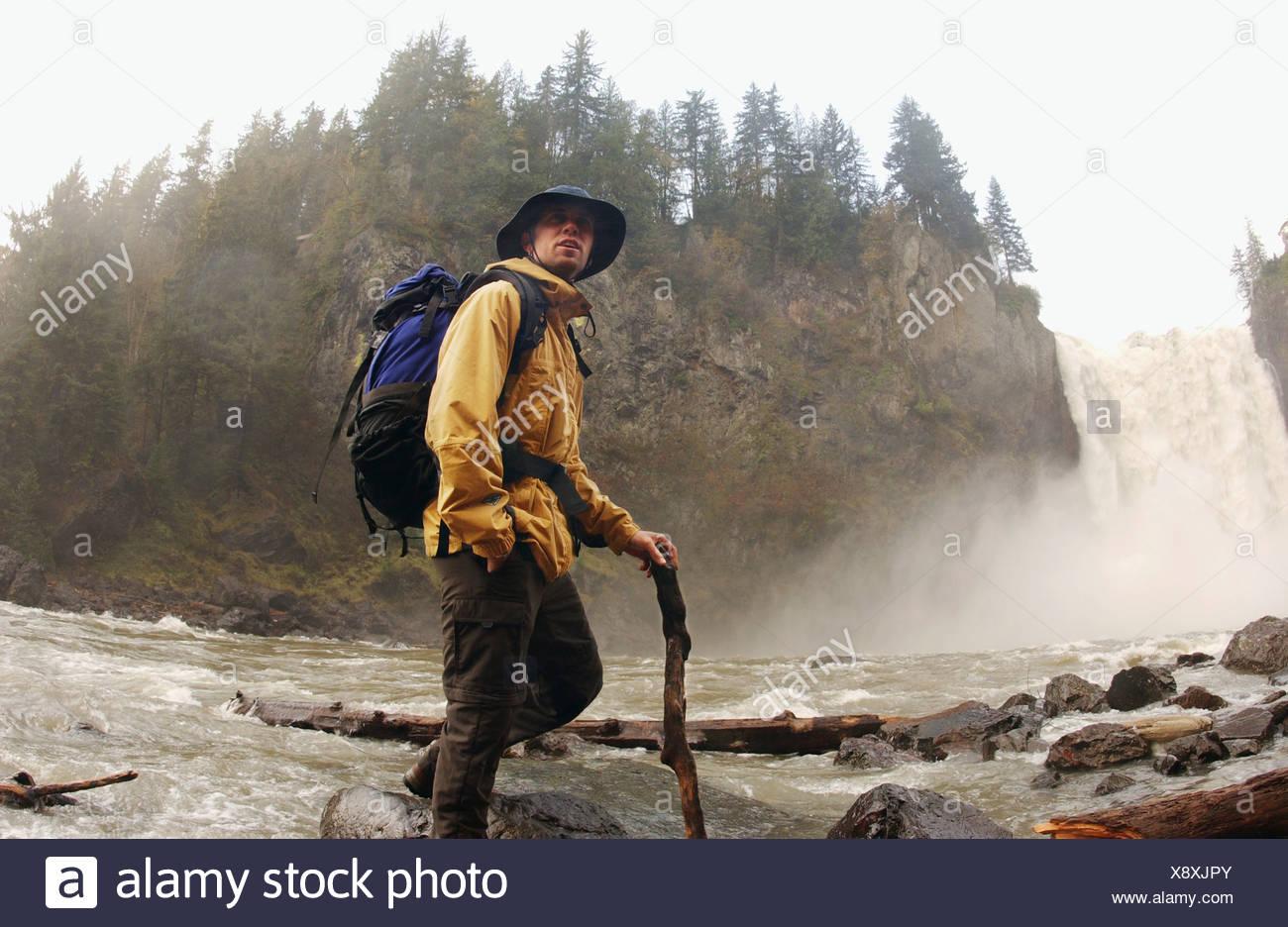 Man hiking near waterfall Stock Photo