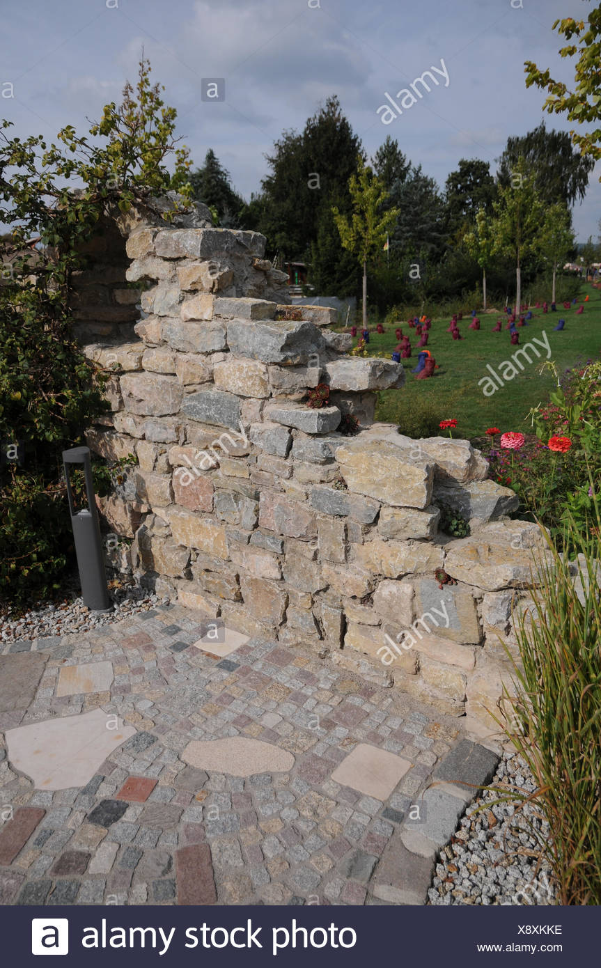 Garden with stone-wall and pavement Stock Photo