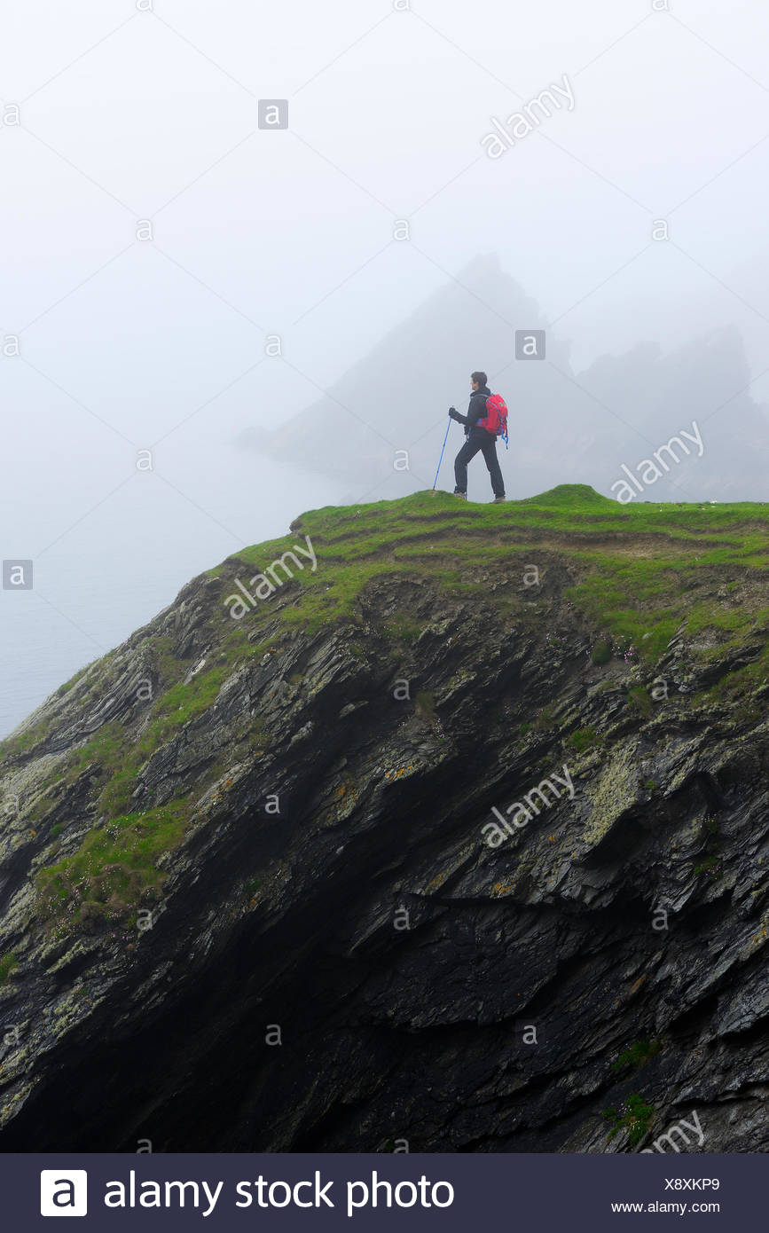 United Kingdom, Scotland, Shetland Islands, Senior woman standing on grassy cliff - Stock Image