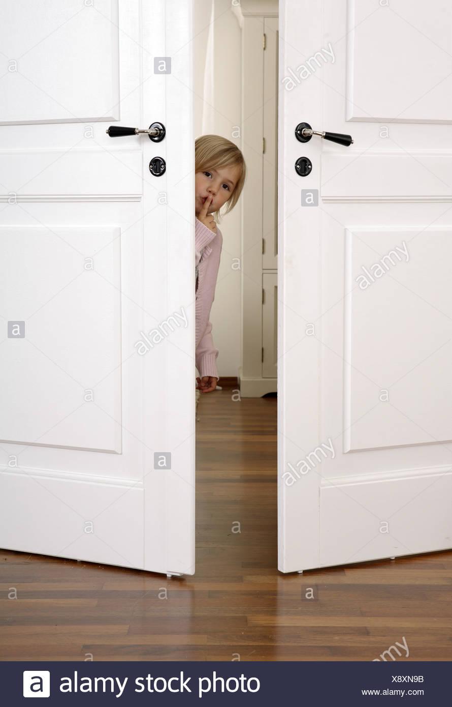 girl door openly curiosity gaze gesture quiet - Stock Image