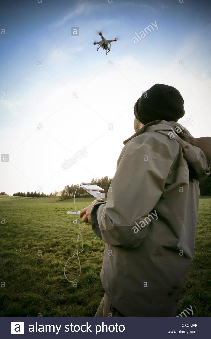 Man on a meadow flying drone - Stock Image