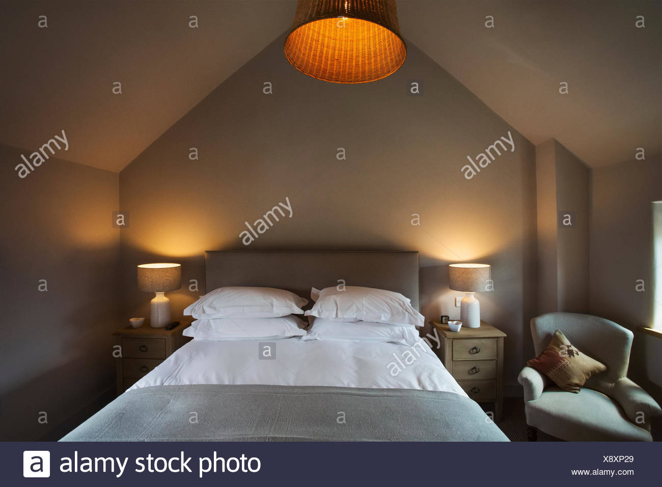 A cosy bedroom decorated in neutral colours, with a double bed and bedside lights on. Hospitality. - Stock Image