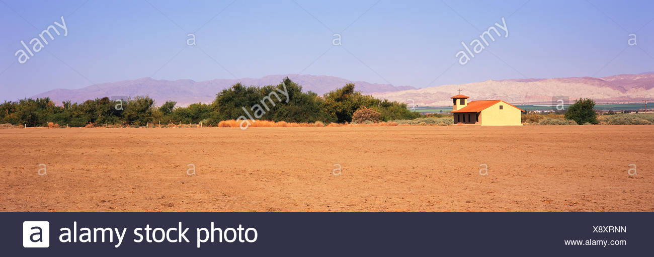A fallow field lies in the foreground with a country church, green fields and mountains beyond, Santa Ynez Valley - Stock Image