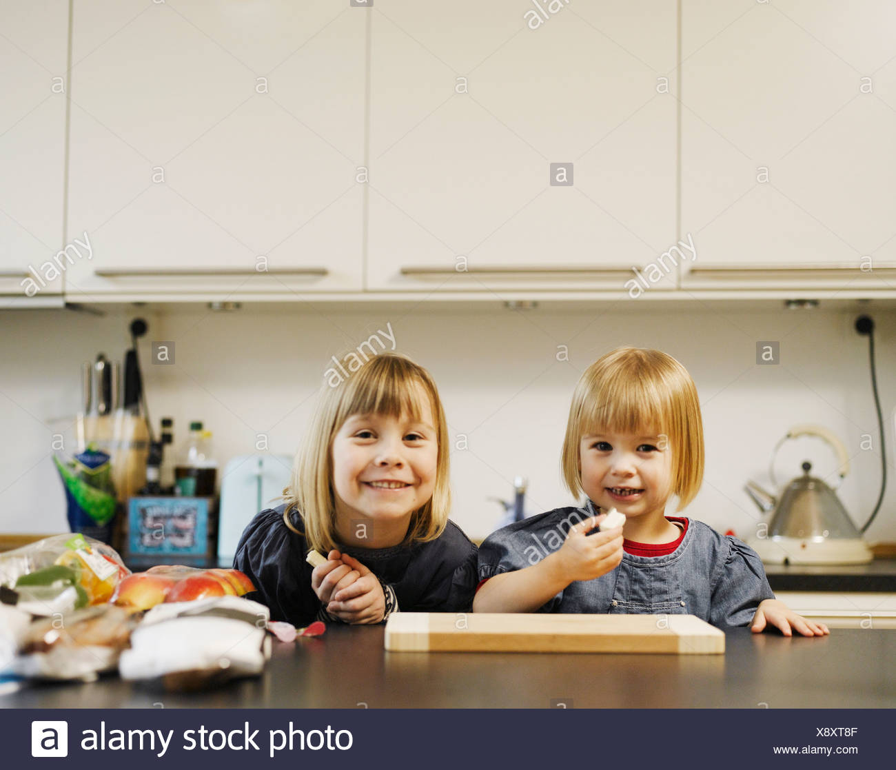 Smiling girls eating in kitchen - Stock Image
