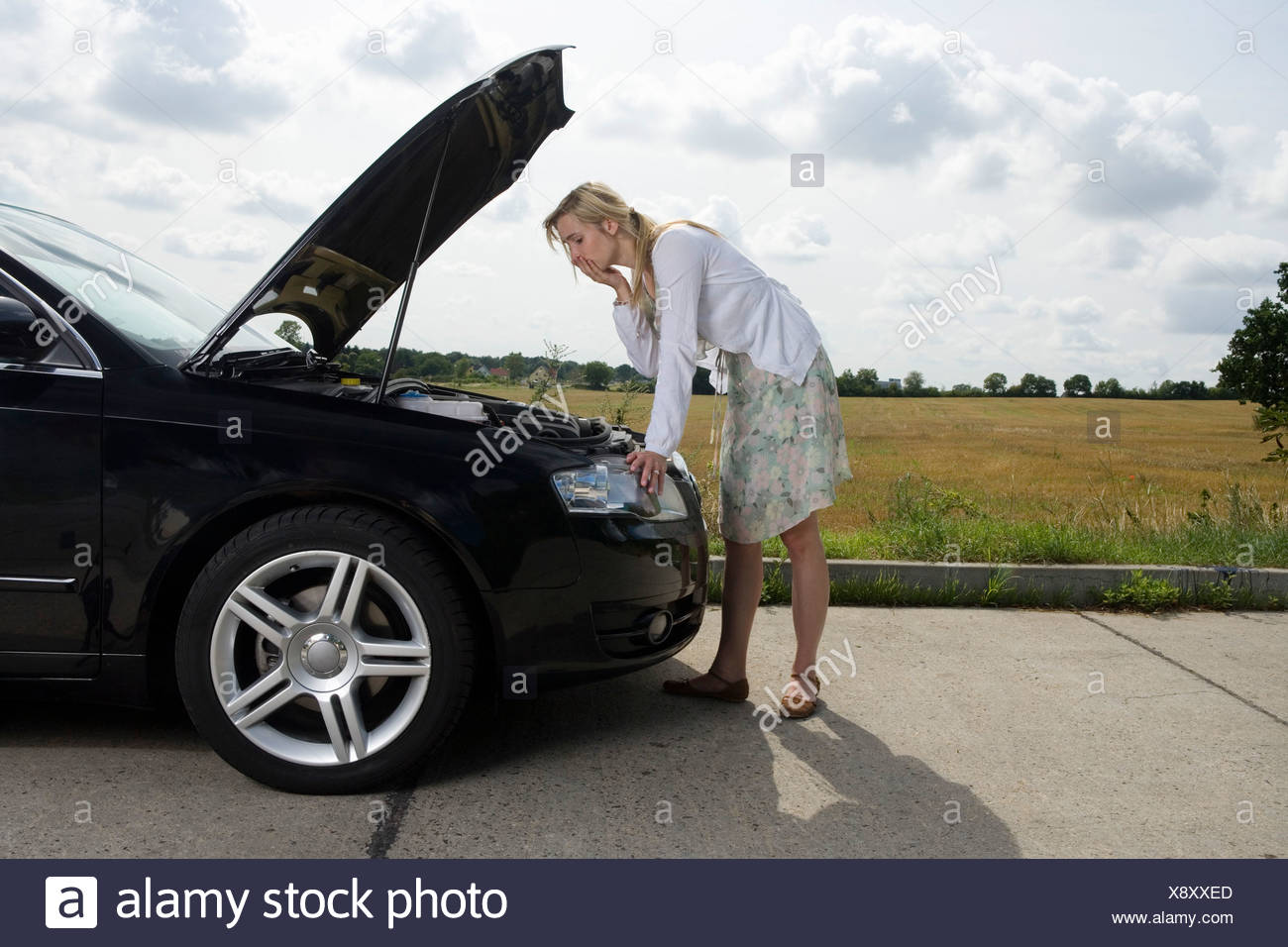 a-woman-leaning-over-an-open-bonnet-at-t