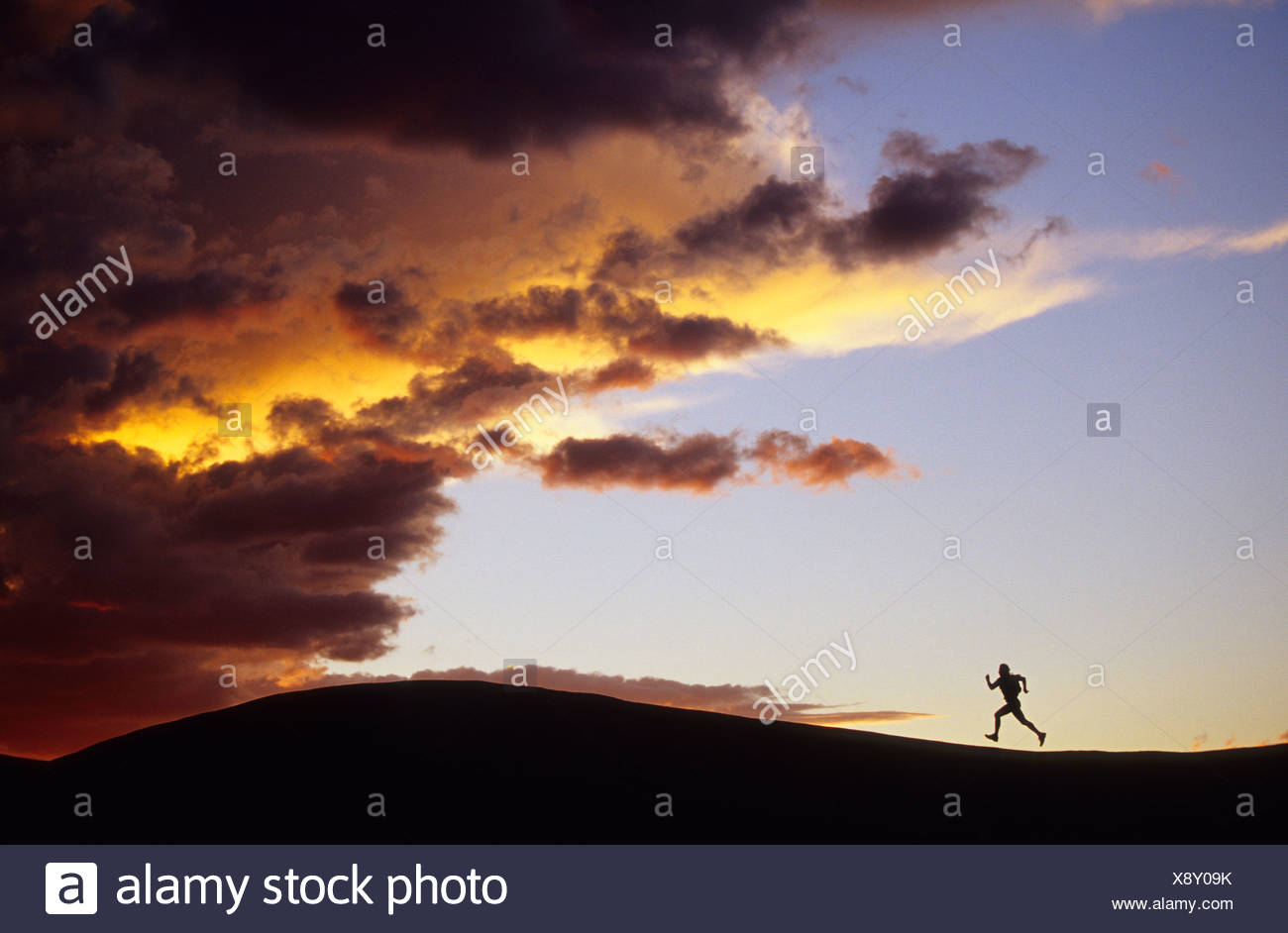 silhouette woman running ridge distance towards - Stock Image