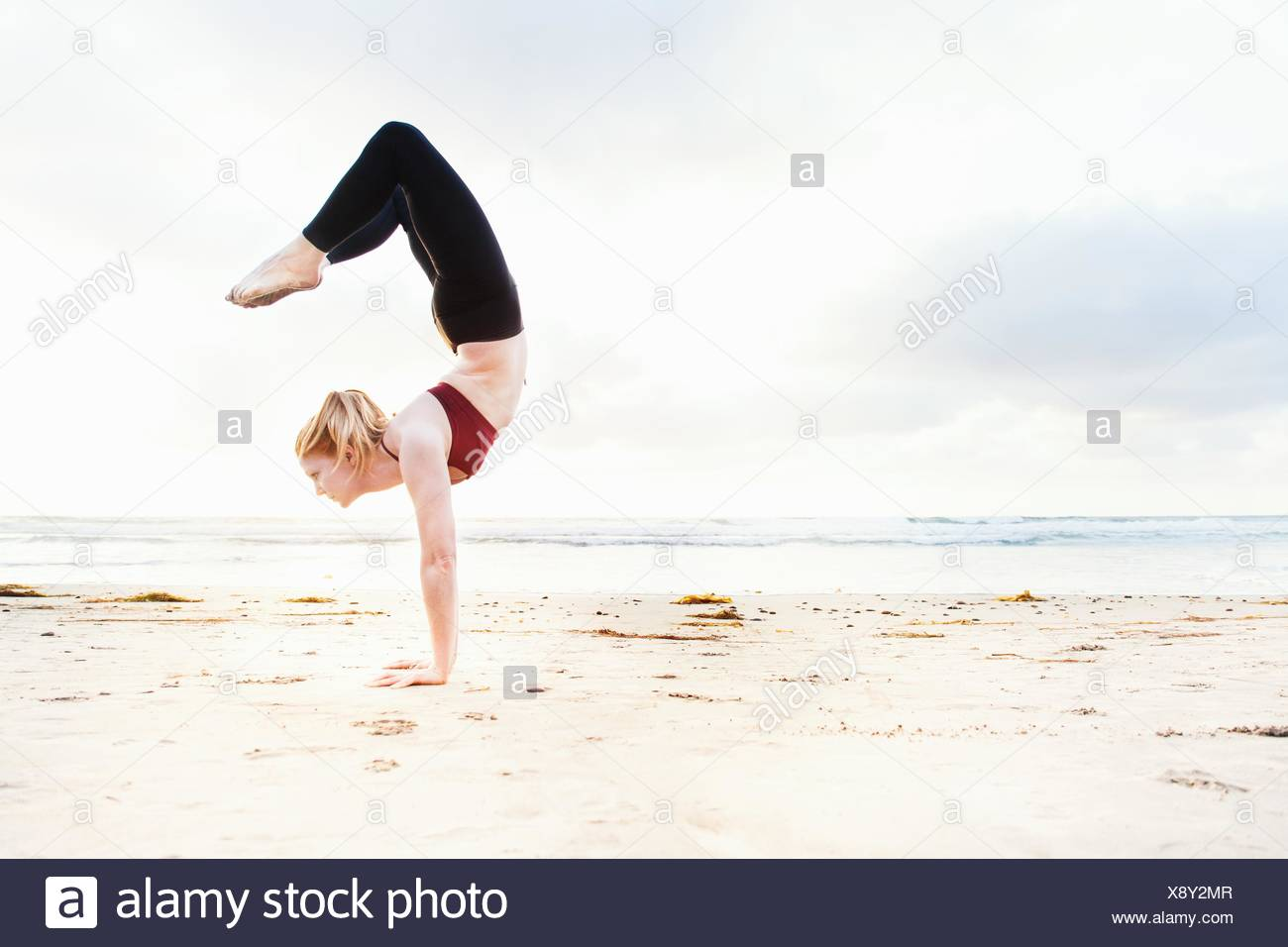 Mid adult woman practicing handstand yoga position on beach - Stock Image