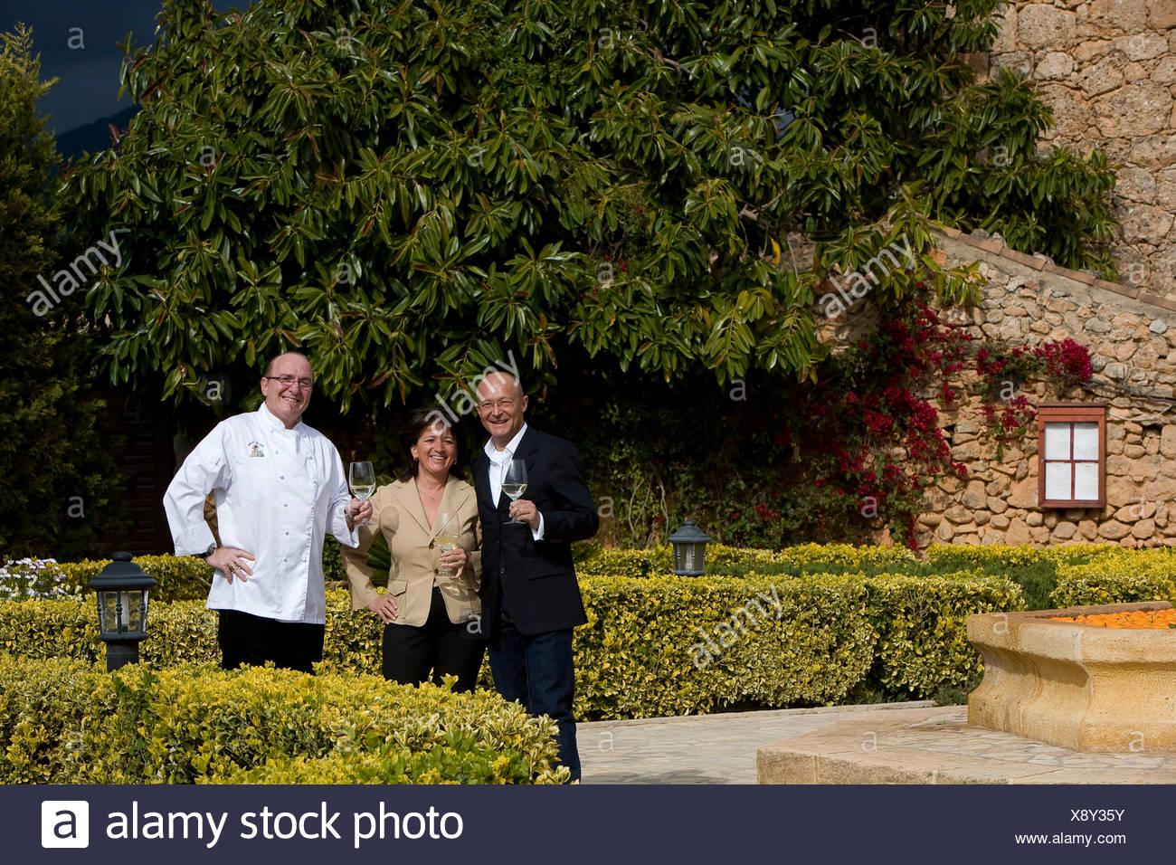 Winemaker Prof. Michael Popp, left, Herta and Peter Himbert, owners of the Molí des Torrent restaurant, Santa María del Camí Stock Photo