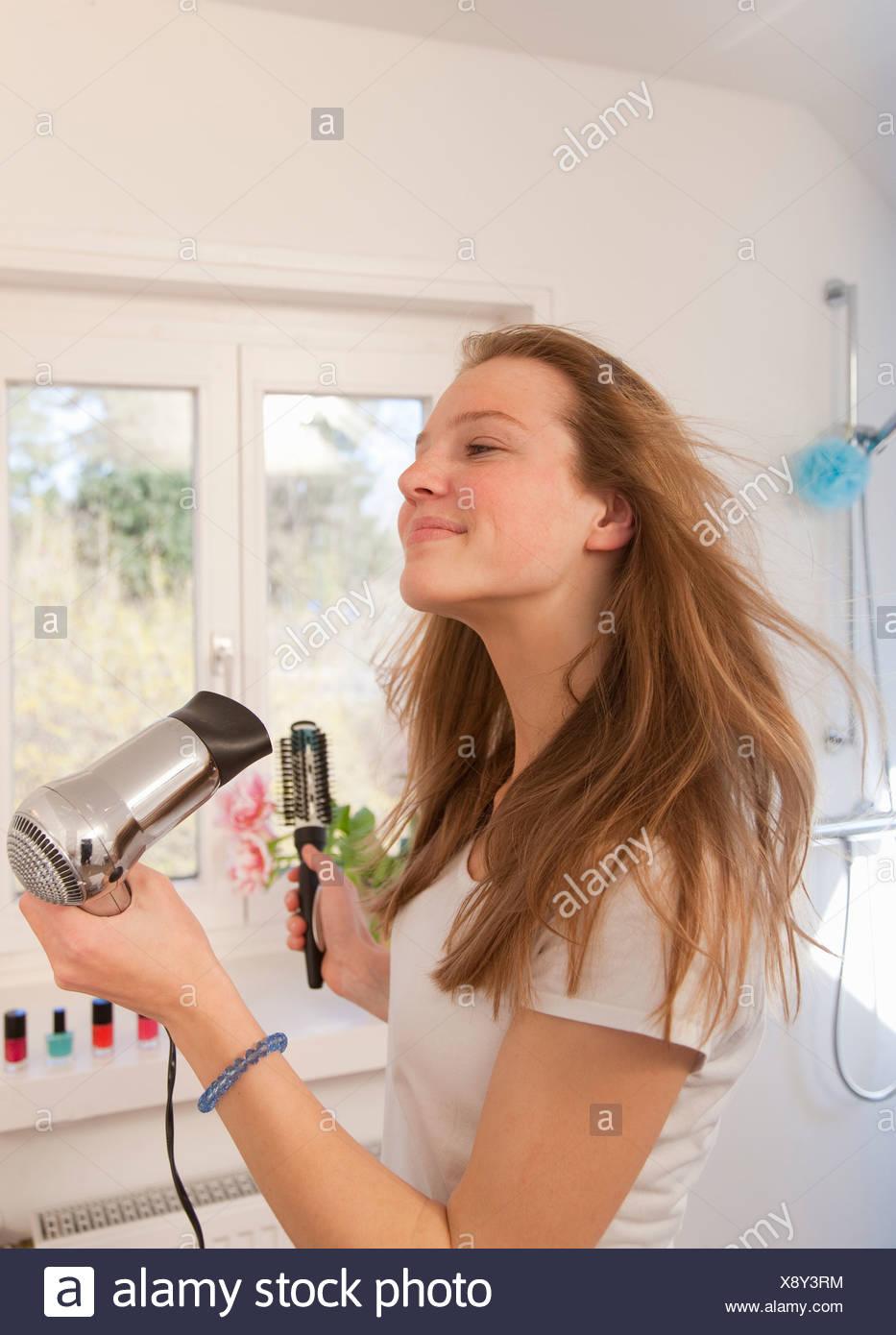 Teenage girl blow drying her hair - Stock Image